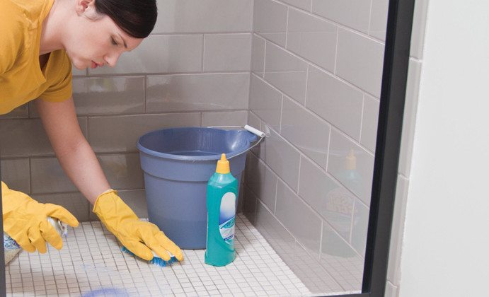 Woman Scrubbing Shower Floor