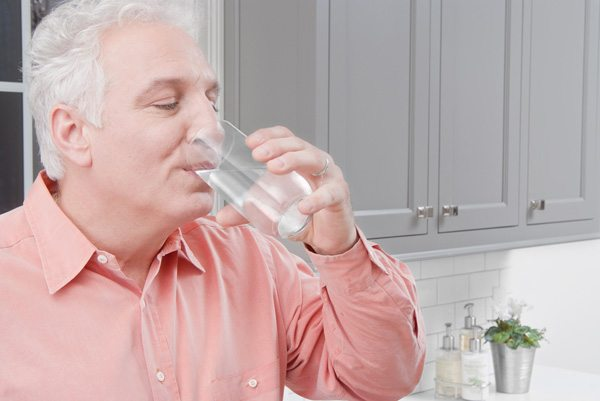 Man Drinking Water from a Clear Glass in Kitchen Horizontal LR