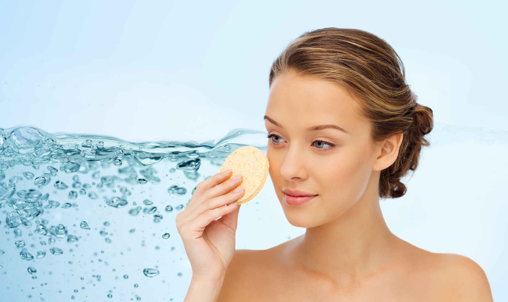 beauty, people, moisturizing, skin care and skincare concept - young woman cleaning face with exfoliating sponge over water splash background